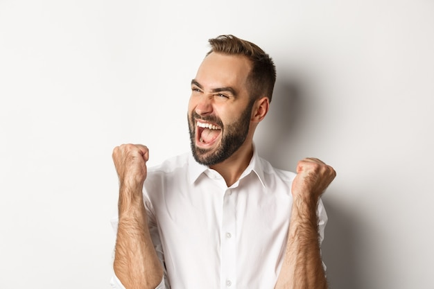Primo piano dell'uomo caucasico di successo che si rallegra, facendo pompare il pugno e gridando di gioia, guardando a sinistra, vincendo, in piedi