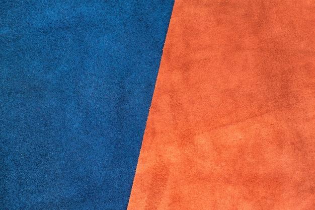 半分の比率のテクスチャの背景でスエードのネイビーブルーとオレンジの革を分割して閉じる