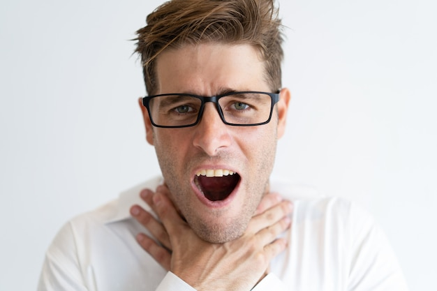 Close-up of suffocating young businessman wearing glasses