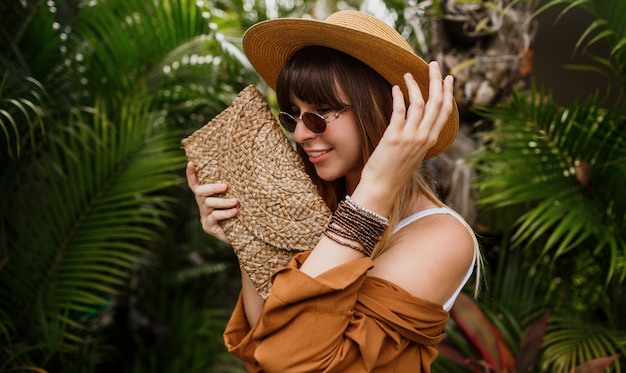 Close up summer fashionable  portrait of brunette woman in straw hat posing on tropical palm leaves