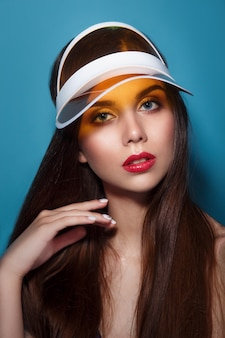 Close-up summer portrait of a beautiful young woman with red lips wearing yellow sun visor.