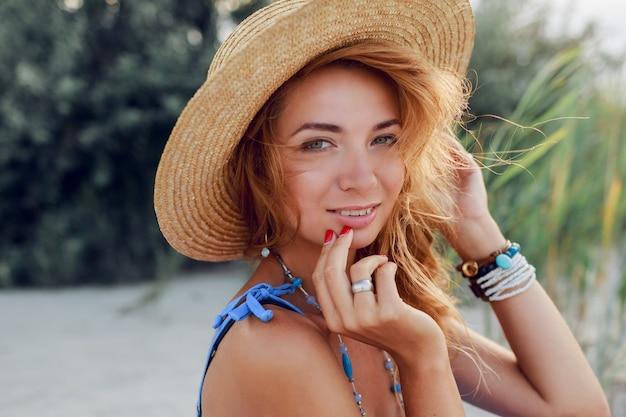 休暇で太陽が降り注ぐビーチでリラックスした麦わら帽子で陽気な美しい女性の夏の肖像画を閉じます。トロピカルムード。