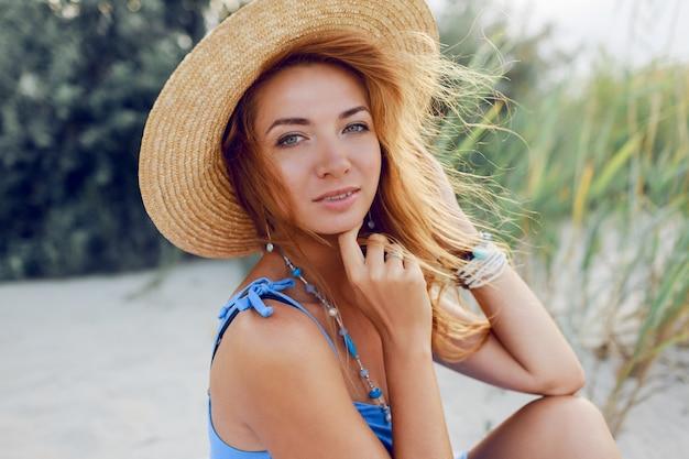 休暇の太陽が降り注ぐビーチでリラックスした麦わら帽子の陽気な美しい女性の夏の肖像画を閉じます。