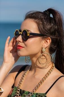 大きな流行のアクセサリーとイヤリングでスタイリッシュな女性の夏の肖像画を閉じます。
