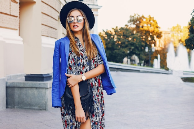 Close up sunny lifestyle portrait of elegant casual woman in black hat, bright dress and blue jacket on shoulders walking  on european streets. fashion and shopping  concept.