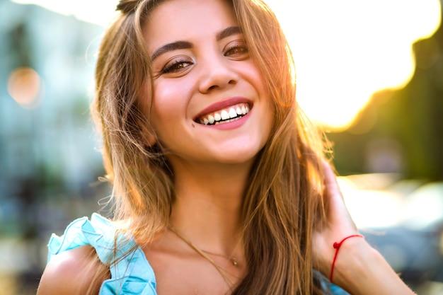 Закройте солнечный портрет красивой великолепной женщины с естественным макияжем и большой удивительной улыбкой, смотрящей в камеру, ярким солнечным светом, позитивным настроением.