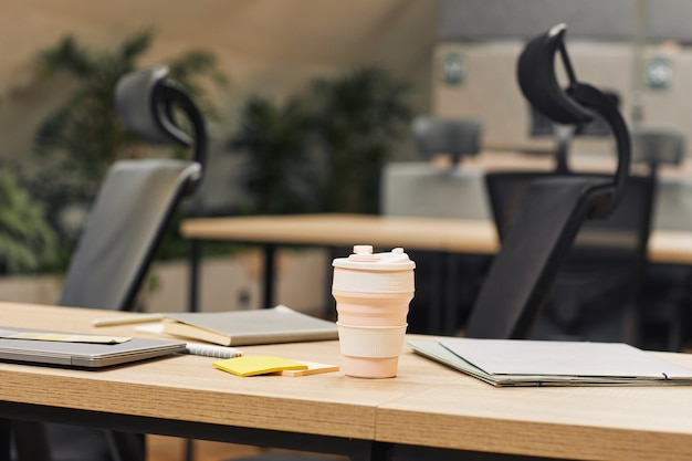 Close up surface image of modern open space office decorated with plants, focus on coffee cup on wooden table in foreground, copy space