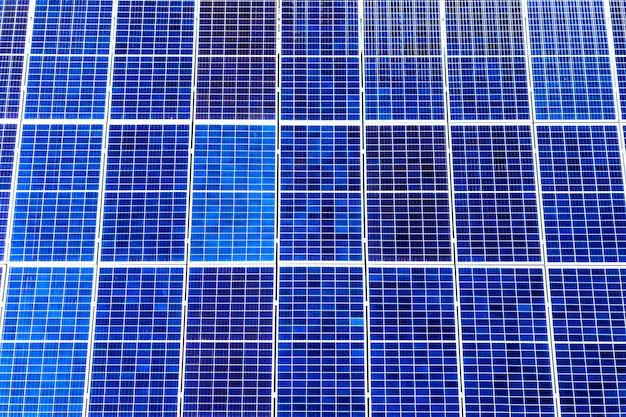 Поверхность крупным планом освещенных солнцем синих блестящих солнечных фотоэлектрических панелей. система производства возобновляемой чистой энергии. концепция производства возобновляемой экологической зеленой энергии.