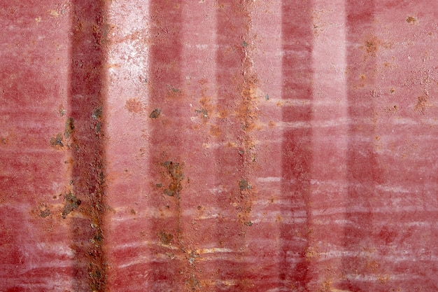 Close-up surface of steel barrel burgundy color with signs of decaying, corrosion, rust or scratches.