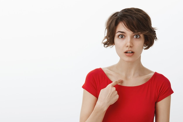 Close-up of surprised and confused woman being chosen, pointing at herself clueless