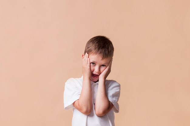 Close-up of surprised cute boy with mouth open standing near beige colored wall