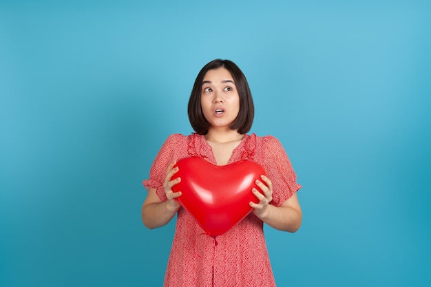 Close up surprised excited asian woman holding red heart shaped balloon