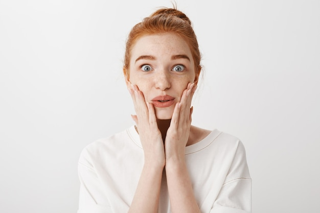 Close-up of surprised and excited girl looking at something awesome