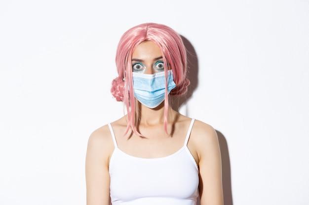 Primo piano della ragazza sorpresa in parrucca rosa e mascherina medica che guarda l'obbiettivo stupito