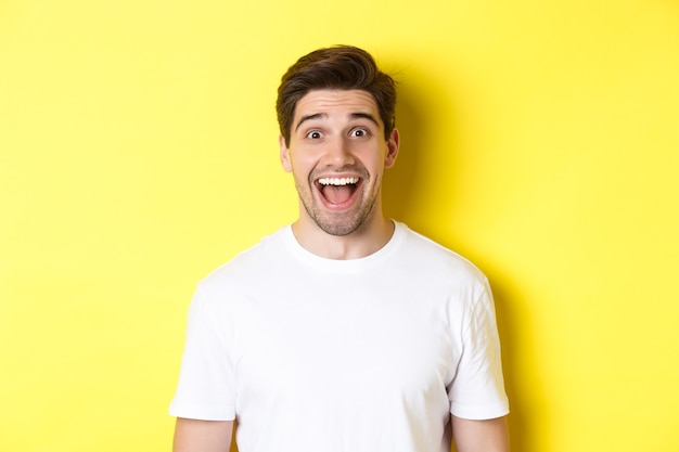Close-up of surprised handsome guy reacting to great news, standing over yellow background in white t-shirt.