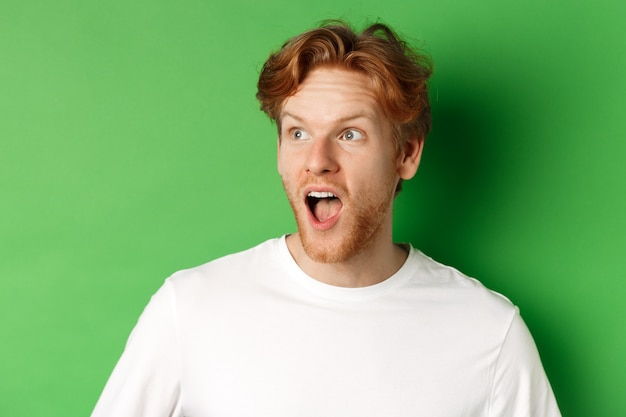Close up of surprised and impressed redhead man checking out promotion offer, looking left with dropped jaw, standing over green background.