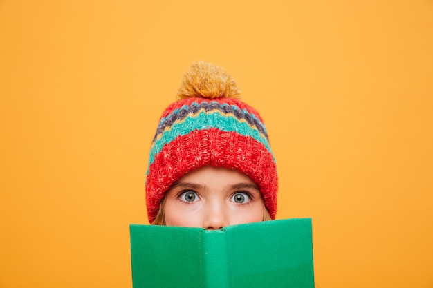 Close up surprised young girl in sweater and hat hiding behind the book and looking at the camera over orange