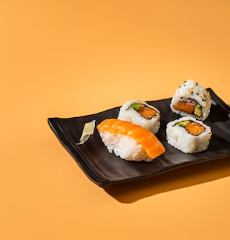 Close up sushi mix on yellow background