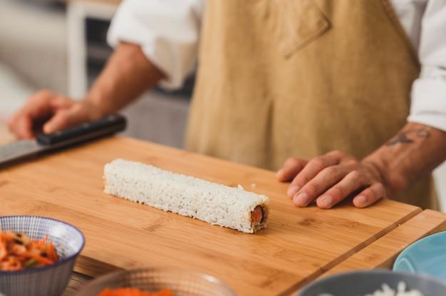 쌀 채식주의 자로 롤을자를 준비가 된 일본 식당 장의 손에 초밥 준비를 닫습니다.