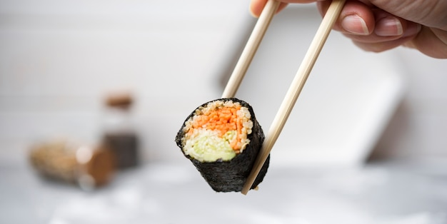 Close-up sushi roll with veggies held in chopsticks