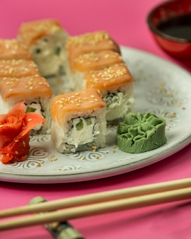 Close up of sushi rolls covered with salmon served with wasabi nad ginger