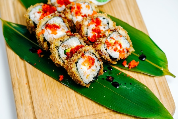 Close up of sushi rolls garnished with red tobiko served on leaves