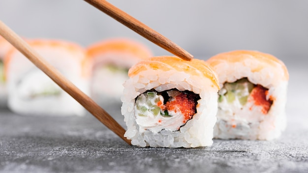 Close-up sushi rolls with chopsticks