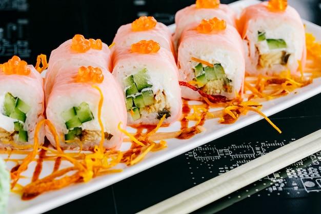 Chiuda su dei rotoli di sushi con il cetriolo e il pesce conditi con il tobiko rosso
