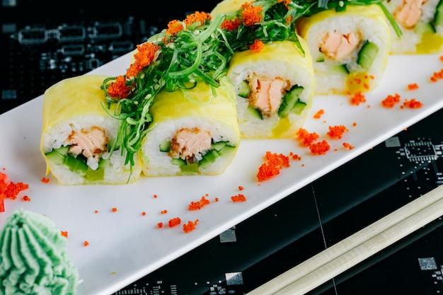 Primo piano di involtini di sushi con salmone fritto e cetriolo condita con alghe e tobiko rosso