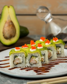 Close up of sushi rolls with shrimp, cucumber covered with avocado