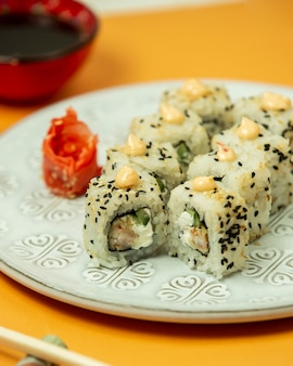 Close up of sushi rolls with shrimp, cucumber covered with sesame