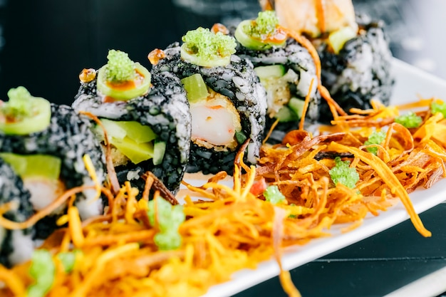 Close up of sushi rolls with tempura and avocado covered with black dyed rice