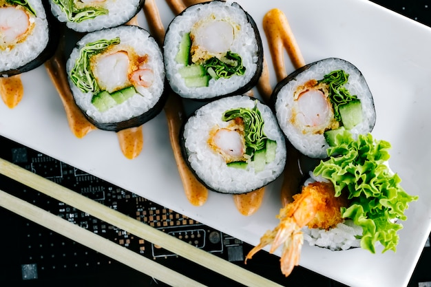 Close up of sushi rolls with tempura cucumber and lettuce