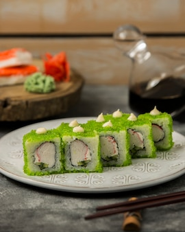 Close up of sushi set with crab sticks, cucumber, covered in green tobiko