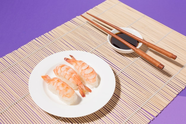Close-up sushi and soy sauce with chopsticks