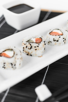 Close-up of sushi with soya sauce in bowl on place mat