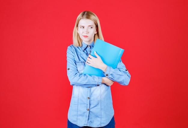 Крупным планом подозрительная студентка-подросток держит синюю папку с документами и выглядит обеспокоенной