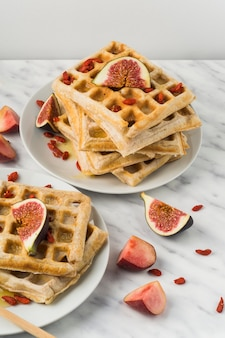 Close-up of sweet belgian waffles; and fig in plate over white background