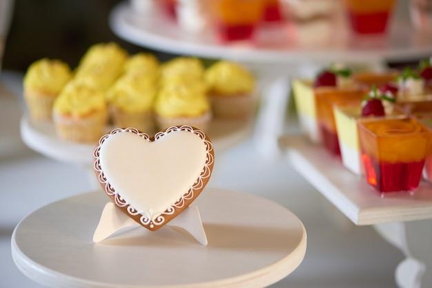 Il primo piano di un biscotto dolce di pan di zenzero, ricoperto di glassa bianca, si trova sul supporto di legno davanti al candybar festivo con cupcakes gialli e gelatine ai frutti di bosco, decorato con lamponi freschi.