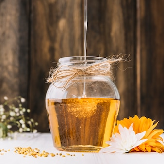 Close-up of sweet honey dripping in glass jar with flower on desk