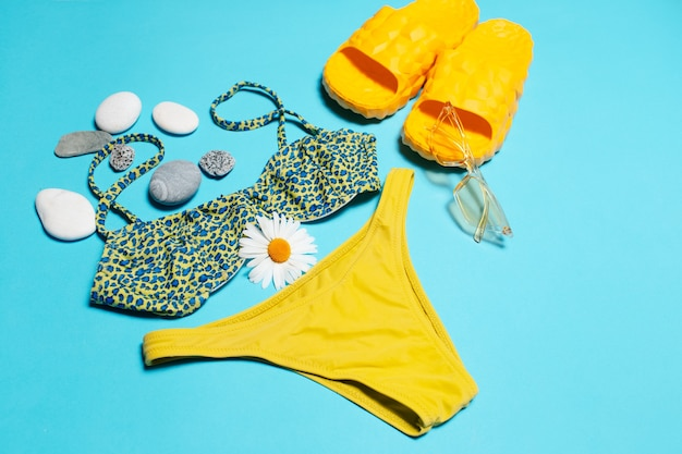 Close-up of swimsuit, sunglasses and slippers decorated with pebbles and chamomile flower