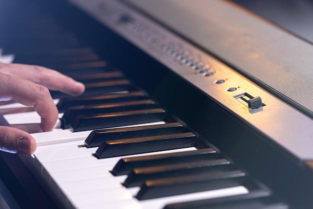 Primo piano di un sintetizzatore o di un tasto di pianoforte in una splendida illuminazione scenica.