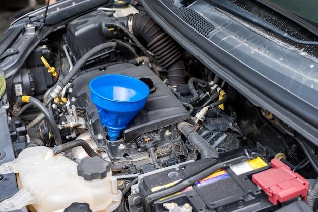 Крупный план замена синтетического масляного картера в передней части двигателя