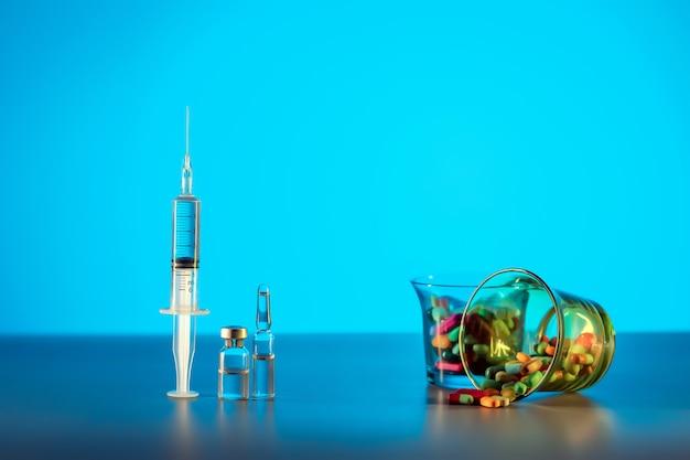 クローズアップ:透明な液体のシリンジ、薬の入ったアンプル、ガラスのマルチカラータブレット。予防接種と薬。健康管理