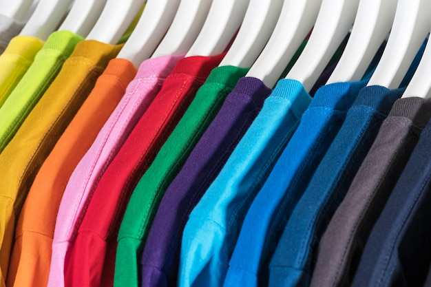 Close up of t-shirts, clothes on hangers on white