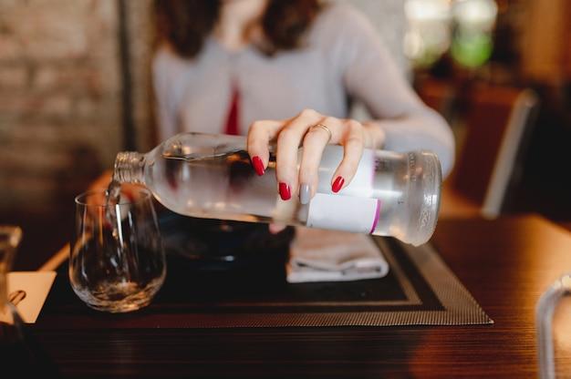 レストランのクローズアップテーブルの設定。ガラスに真水を注ぐボトルを持っている認識できない女性の手。