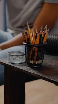 Primo piano del tavolo con strumenti artistici e matite colorate per un concetto di disegno professionale nello spazio dello studio d'arte. artista creativo afroamericano che lavora su tela capolavoro per progetto