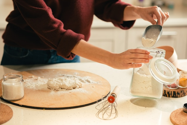 Close up of the table with dough on cutting board and woman carefully taking flour from the jar
