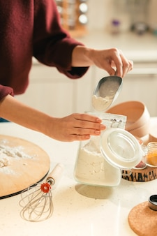 Close up of the table with glass jar of flour and woman holding a flour scoop