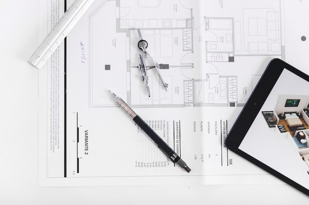 Close-up tablet and drafting tools on blueprint